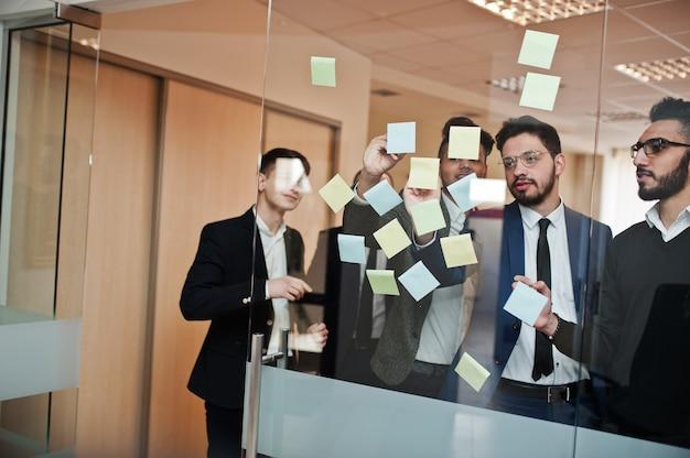 Bedrijfsmensen die op glas met kleurrijke document nota's richten