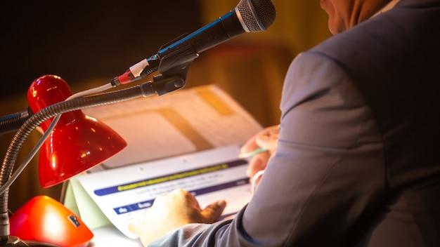 Bedrijfsmensen die op seminariepaneel spreken met microfoon