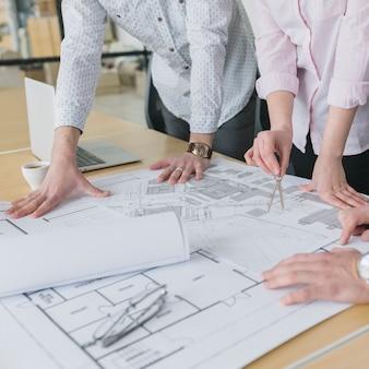 Bedrijfsmensen die plannen in bureau bekijken