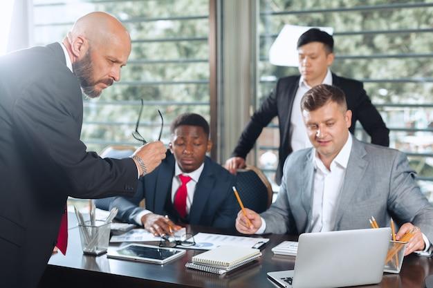 Bedrijfsmensen die rond een bestuurskamerlijst samenkomen die strategie bespreken