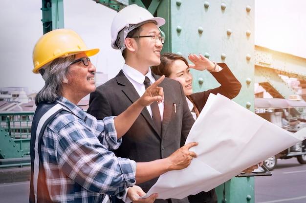 Bedrijfsmensen die tablet en administratie in zwarte reeks, plaidoverhemd en helm houden.