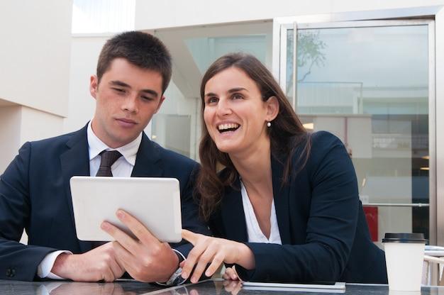 Bedrijfsmensen die tablet gebruiken en bij bureau in openlucht werken