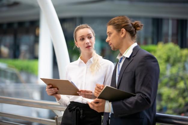 Bedrijfsmensen die terwijl status op voetgangersbrug bespreken