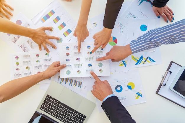 Bedrijfsmensen die vingers aan document grafieken op lijst in vergaderzaal richten.