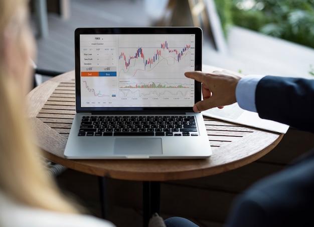 Bedrijfsmensen in een vergadering die op grafieken en statistieken van de financiële groei richten