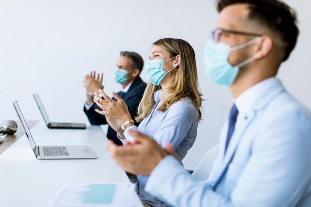 Bedrijfsmensen met beschermingsmaskers die handen klappen na succesvolle commerciële vergadering in het moderne bureau