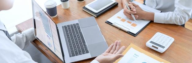 Bedrijfsmensen spreken besprekend met medewerker planning die de grafieken en grafieken van financiële documentgegevens analyseren in vergadering en succesvol groepswerkconcept.