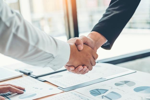 Bedrijfsmensencollega's die handen schudden die de analyseconcept van de planningsstrategie ontmoeten
