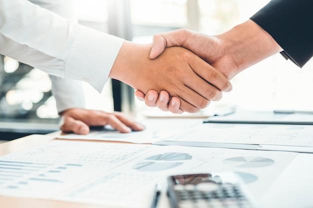 Bedrijfsmensencollega's die handen schudden die het concept van de planningsstrategieanalyse ontmoeten