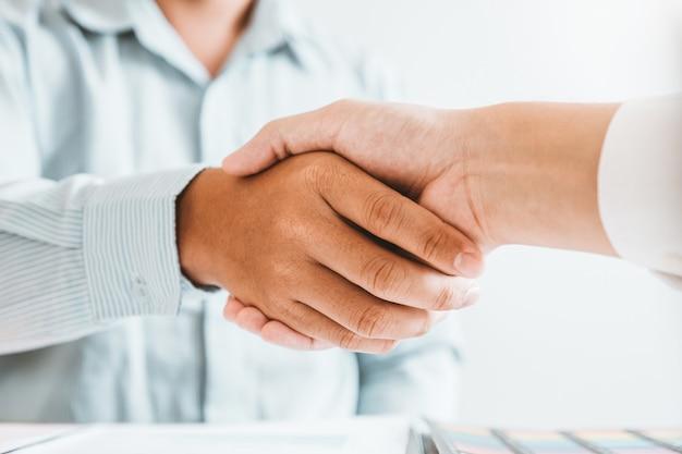 Bedrijfsmensencollega's die handen tijdens een vergadering schudden om overeenkomst voor de analyse van de nieuwe partner planningsstrategie te ondertekenen