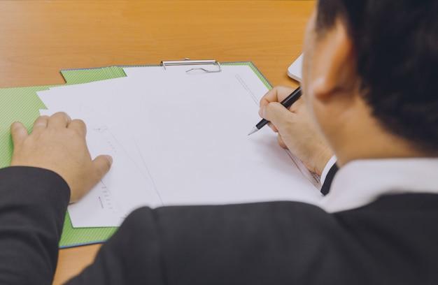 Bedrijfsmensenhand die een document ondertekenen
