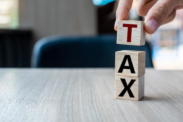 Bedrijfsmensenhand die houten kubus met belastingstekst houden