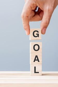 Bedrijfsmensenhand die houten kubusblok met het bedrijfswoord van het doel houden. doel, doel, missie, actie en planconcept