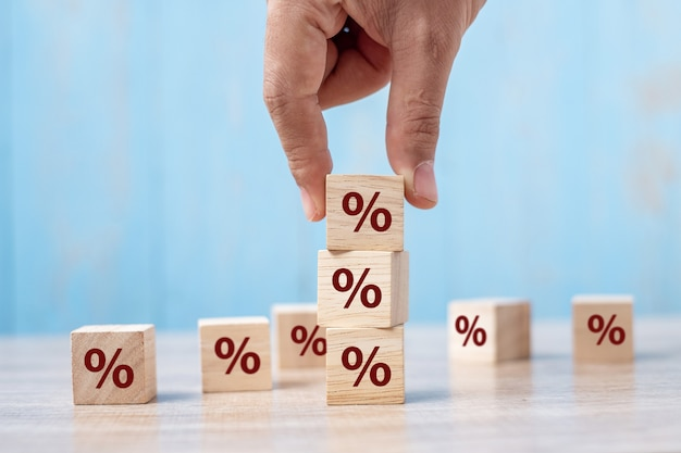 Bedrijfsmensenhand die houten kubusblok met het pictogram van het percentagesymbool zetten.