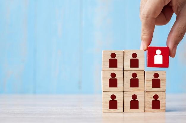Bedrijfsmensenhand die of rood houten blok met persoon plaatsen trekken