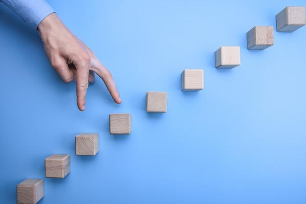 Bedrijfsmensenhand die zijn vingers lopen de stappen op een carrièreladder op