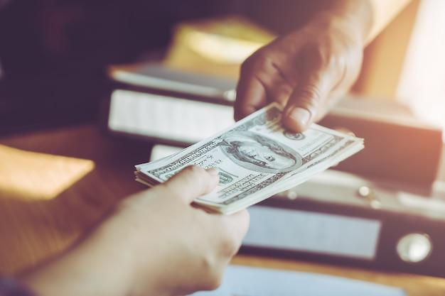 Bedrijfsmensenhanden die geld over zaken overhandigen