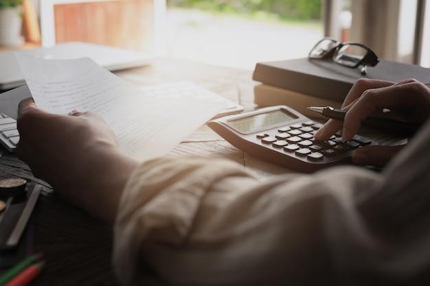 Bedrijfsmensenhanden die het bankboekje van de besparingsrekening met calculator houden, rekening en besparingsconcept.