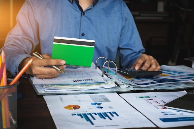 Bedrijfsmensenhanden die spaarrekeningbankboekje met calculator houden