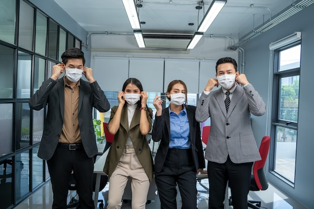Bedrijfsmensenteam dat masker draagt ter bescherming van de coronavirusziekte die samenwerkt.