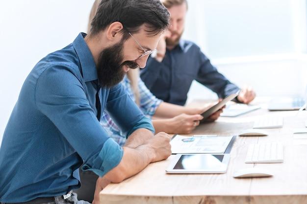 Bedrijfsmensgebruik van de digitale tablet om met financiële documenten te werken