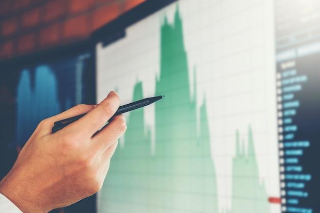 Bedrijfsmensinvesteringshandelaar die en de voorraad van de analysegrafiek bespreken bespreken