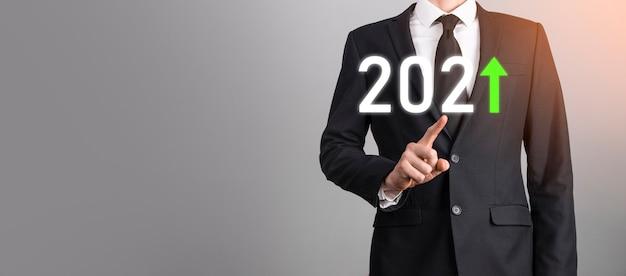 Bedrijfsontwikkeling tot succes en groeiend groeijaar 2021-concept. plan bedrijfsgroeigrafiek in jaar 2021-concept. zakenmanplan en toename van positieve indicatoren in zijn bedrijf