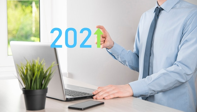 Bedrijfsontwikkeling tot succes en groeiend groeijaar 2021-concept. plan bedrijfsgroeigrafiek in jaar 2021-concept. zakenmanplan en toename van positieve indicatoren in zijn bedrijf.