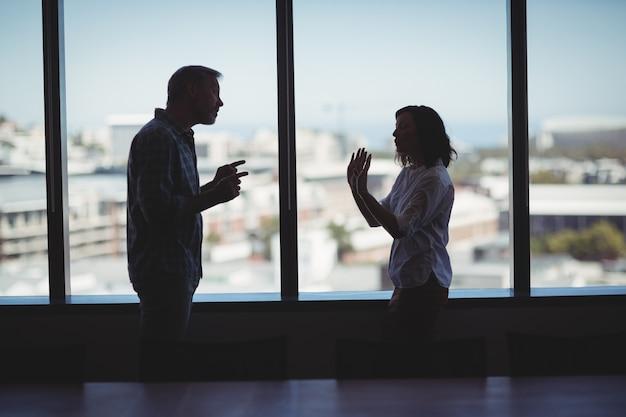 Bedrijfspaar die dichtbij het venster debatteren