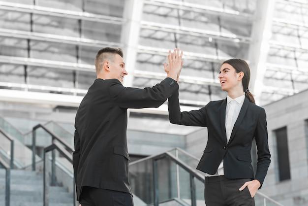 Bedrijfspaar die hoge vijf doen