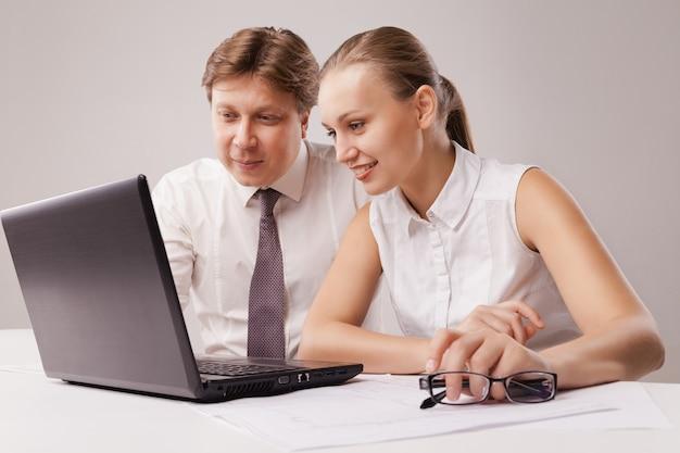 Bedrijfspaar die laptop met behulp van. geïsoleerd op witte achtergrond.