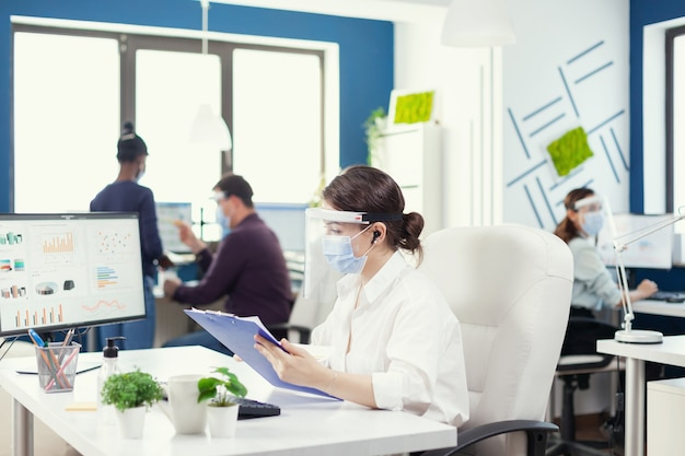 Bedrijfspersoon die draadloze hoofdtelefoons gebruikt om met collega's van een andere afdeling te praten. werknemers met vizieren die in de werkruimte van een bedrijfsbedrijf werken en de sociale afstand respecteren, gegevens analyseren en gr