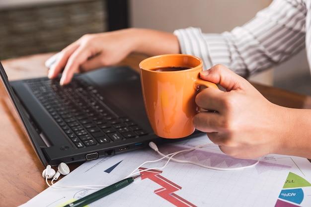 Bedrijfspersoon die op laptop computer werkt en koffie drinkt.