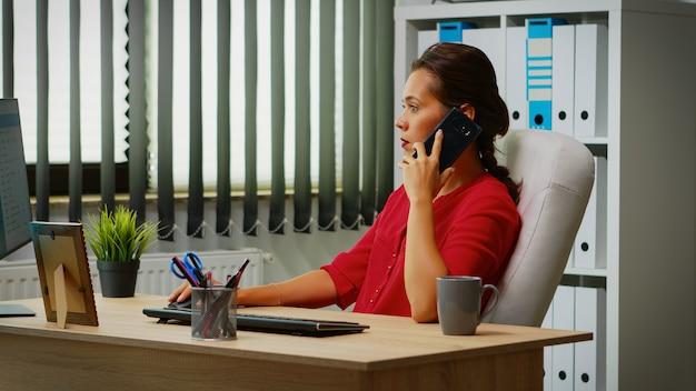 Bedrijfspersoon die op slimme telefoon met collega bespreekt. spaanse ondernemer werkt in een modern kantoor, werkplek in een persoonlijk zakelijk bedrijf dat op een mobiele telefoon spreekt en naar het bureaublad van de computer kijkt