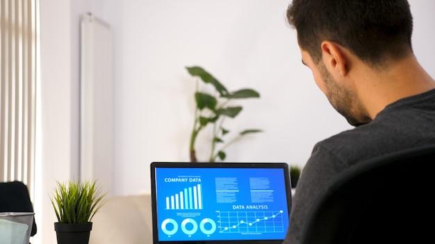 Bedrijfspersoon die op zijn laptop werkt en grafiekgegevens in zijn woonkamer bekijkt