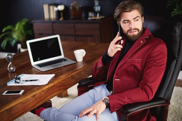 Bedrijfspersoon die telefonisch praat op kantoor aan huis