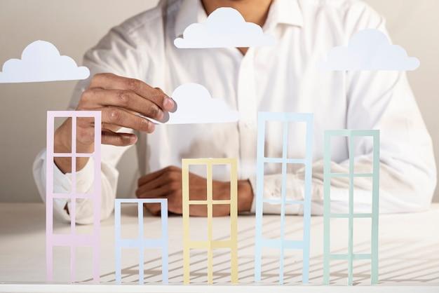 Bedrijfspersoon en papieren gebouwen en wolken