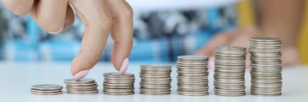 Bedrijfspersoon loopt vingers op biefstuk met munten in de richting van toenemende winst