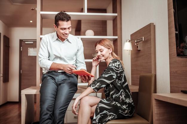 Bedrijfsplan. echtgenoot die zijn creatieve businessplan toont aan zijn aantrekkelijke vrouw die stijlvolle kleding draagt