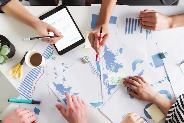 Bedrijfsplanningsproces met collega's of partners die samen aan tafel zitten met verschillende afbeeldingen, grafieken, documenten en tablet die project, budget, analyse bespreken en plannen