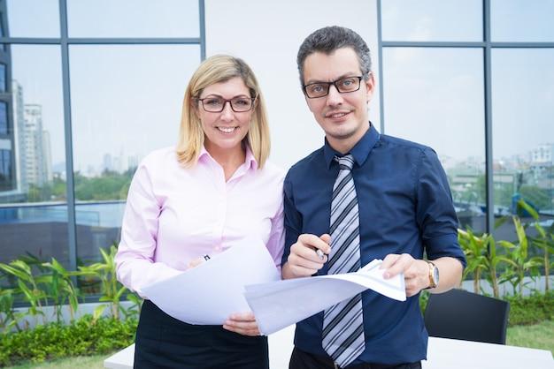 Bedrijfsportret van twee bedrijfsdeskundigen met documenten in openluchtdocumenten buiten bureau.