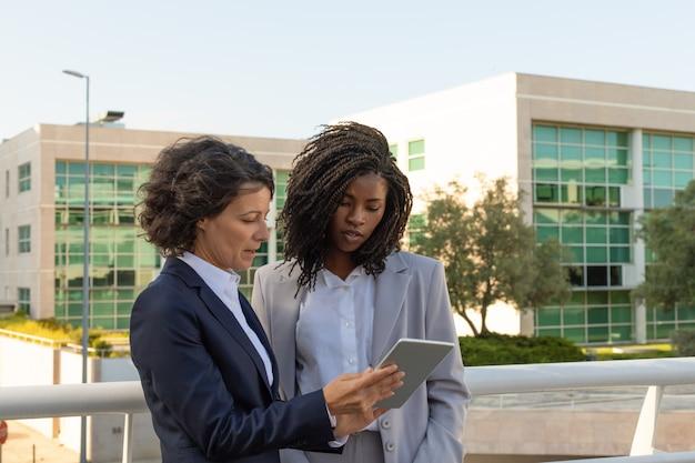 Bedrijfsprofessional met tablet raadplegende collega