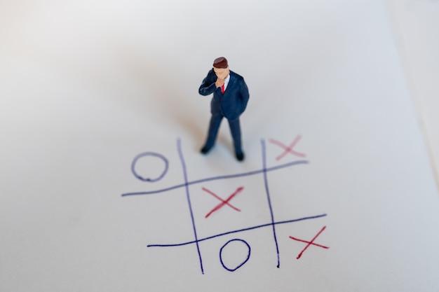 Bedrijfsrichting en planningsconcept. zakenman miniatuurcijfer die zich op papier met ox-spel bevinden