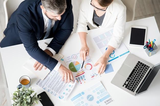 Bedrijfsspecialisten die de voortgang analyseren tijdens het bekijken van grafieken