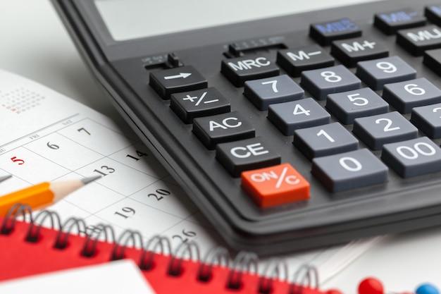 Bedrijfsstilleven met calculator op lijst in bureau.