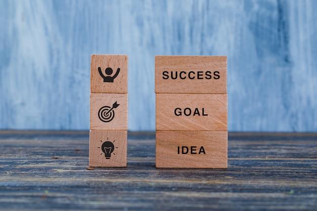 Bedrijfsstrategieconcept met houten blokken op houten en grungy blauw zijaanzicht als achtergrond.