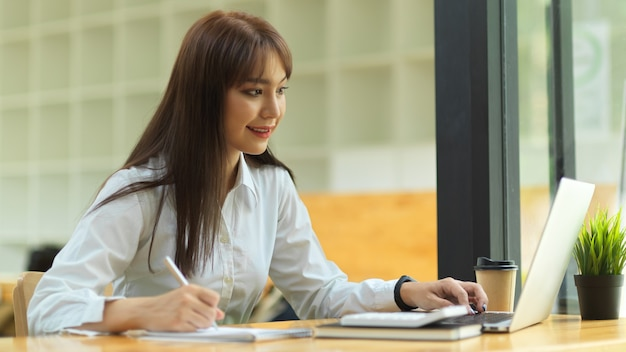 Bedrijfsstudent die lezing geeft over online les via draagbare laptop bij bibliotheek e-learning concept