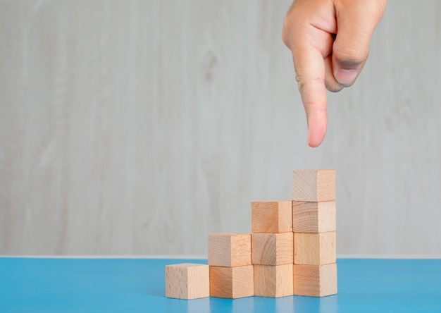 Bedrijfssuccesconcept op blauw en grijs lijst zijaanzicht. vinger die stapel houten kubussen toont.