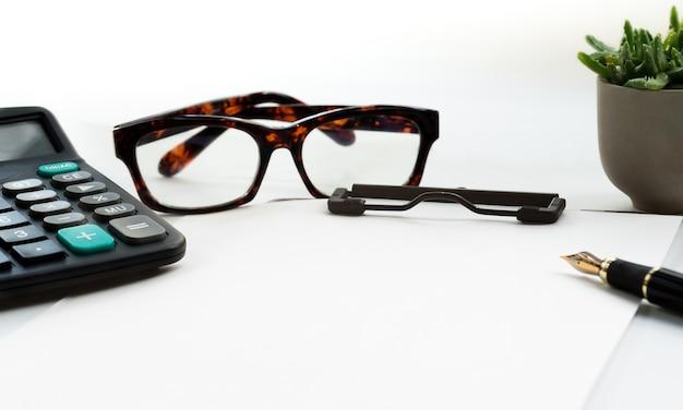Bedrijfsvoorwerpen, klembord met leeg blad van document, pen, glazen en calculator