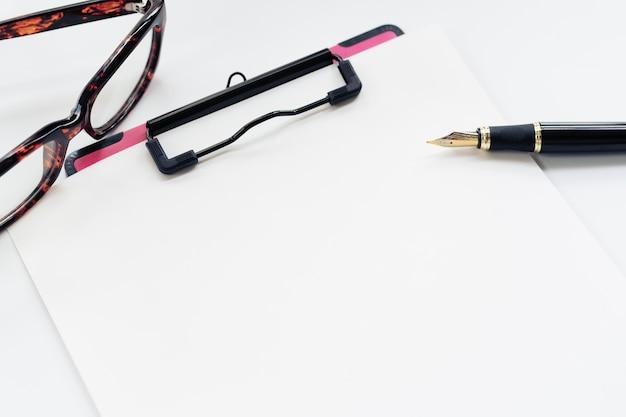 Bedrijfsvoorwerpen, klembord met leeg blad van document, pen, glazen op witte achtergrond